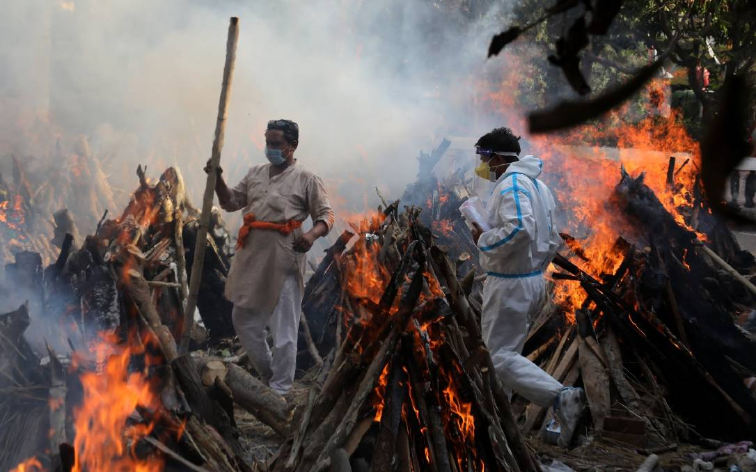 Tough times: Relatives stand next to the burning funeral pyres of those who died due to COVID-19 at Ghazipur cremation ground in New Delhi. Picture: Getty Images